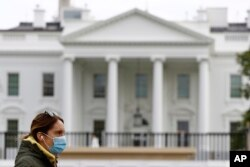 FILE - A woman wearing a face mask walks past the White House in Washington, D.C., April 1, 2020.