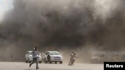 People react as dust rises after explosions hit Aden airport, upon the arrival of the newly-formed Yemeni government in Aden, Yemen, Dec. 30, 2020.
