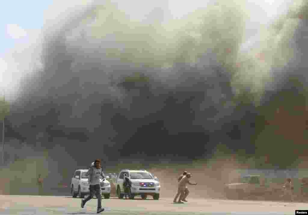 People run as dust rises after explosions hit Aden airport, upon the arrival of the newly-formed Yemeni government in Aden.