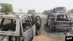 FILE - Burmt cars are seen after a deadly attack by suspected members of the Islamic State West Africa Province (ISWAP) in Auno, Nigeria, Feb. 9, 2020.