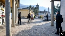 A moment of a funeral service without relatives in the cemetery of Zogno, near Bergamo, Northern Italy, Saturday, March 21, 2020. Italy's tally of coronavirus cases and deaths keeps rising, with new day-to-day highs: 793 dead and 6,557 new cases…