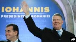 Presiden Romania Klaus Iohannis (kanan) melambaikan tangan didampingi Perdana Menteri Romania Ludovic Orban, di Bucharest, Romania, 24 November 2019.