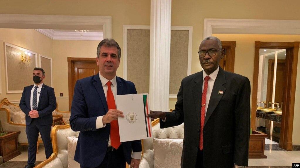 Wasiirka Mukhaabaraadka Israel Eli Cohen (Bidix) iyo Wasiirka Difaaca Sudan Ibrahim Yasin oo dukumintiyo is weydaaranaya kaddib kulan ay ku yeesheen Khartoum January 25, 2021.
