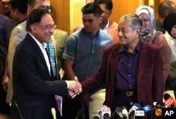 FILE - Malaysian Prime Minister Mahathir Mohamad shakes hand with successor Anwar Ibrahim in Putrajaya, Feb. 22, 2020.