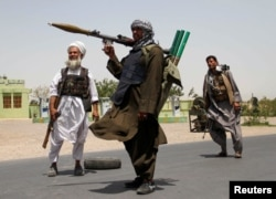 Former Mujahideen hold weapons to support Afghan forces in their fight against Taliban, on the outskirts of Herat province, July 10, 2021.