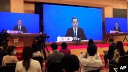 FILE - In this Sunday, May 24, 2020, file photo, China's Foreign Minister Wang Yi is seen broadcasted remotely on big screens at the media center during a press conference held on the sideline of the National People's Congress in Beijing. Wang is…