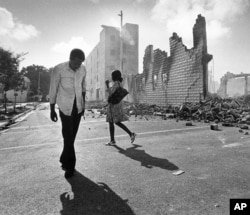 FILE - In this May 19, 1980, photo, people walk past ruins in Miami after rioting over the acquittal of four police officers charged with the 1979 beating death of a black man.