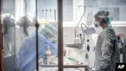 FILE - Medical personnel work in the intensive care unit of a hospital in Brescia, Italy, March 19, 2020.