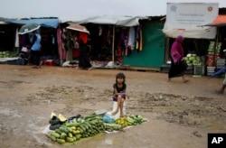 FILE - A Rohingya refugee girl sells vegetables in Kutupalong refugee camp, Bangladesh, Aug. 28, 2018.