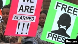 Des manifestants pour la liberté de la presse tiennent des pancartes devant le tribunal de première instance de Harare.