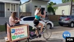루이지애나주 뉴올리언스에서 새라 그랜트 씨가 운전하는 페디캡을 탄 애나 로즈노브스카 씨와 바이올린 연주를 하며 돌아다니고 있다.