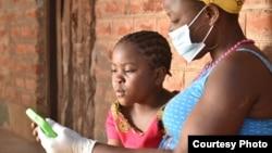 Une élève travaille avec sa mère sur un cours à l'aide d'une tablette fournie par l'organisation caritative britannique Voluntary Services Overseas, au Malawi. (VSO / Craig Mawanga)