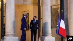 United States Special Presidential Envoy for Climate John Kerry, left, speaks with France's President Emmanuel Macron as he leaves the Elysee Palace in Paris, Wednesday, March 10, 2021.