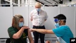 Perdana Menteri Inggris Boris Johnson menyaksikan seorang petugas tanggap darurat menerima vaksinasi Covid-19 di Bristol, Inggris (11/1).