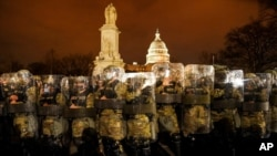 FILE - District of Columbia National Guard stand outside the Capitol, Jan. 6, 2021.