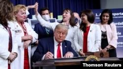 Prezidan Trump ki t ap siyen dekrè yo nan yon seremoni ki t ap dewoule nan La Mezon Blanch nan Washington, DC., vandredi 24 jiyè 2020 an.