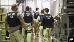 FILE - Immigration and Customs Enforcement (ICE) together with Homeland Security Investigations (HSI) officers prepare to make arrests at an agricultural processing facility in Canton, Mississippi, Aug. 7, 2019.