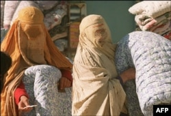 FILE - Afghan women, shown Nov. 19, 1996, in Kabul, wear Taliban-imposed burqas as they wait during a winter relief distribution. Scores of poor Kabul residents, notably women, were regularly seen huddled in front of aid agencies every day.