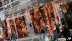 Kaca jendela sebuah restoran yang menjual bebek panggang di Lima, Peru, memantulkan bayangan para pejalan kaki yang melewati jalanan di depannya, di tengah pandemi Covid-19, 11 Juli 2020. (AP Photo/Rodrigo Abd)