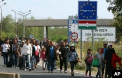 FILE - Migrants and refugees cross the border between Hungary and Austria, near Nickelsdorf, Austria, Sept. 10, 2015.