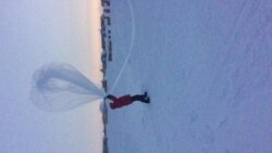 Refael Klein and a colleague launch a weather balloon with an ozonesonde into the Antarctic sky.
