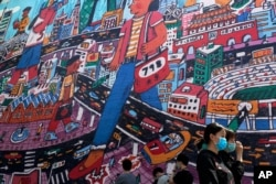 People wearing protective face masks to help curb the spread of the new coronavirus walk by a giant painting depicting the capital city at 798 art district in Beijing, Sunday, April 26, 2020.