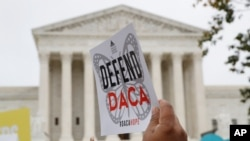 FILE - In this Nov. 12, 2019, photo, people rally outside the Supreme Court. The Trump administration must accept new applications for the DACA program that protects some young immigrants from deportation, a federal judge ruled Dec. 4, 2020.