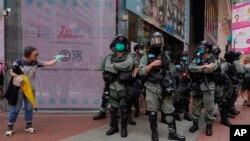 Policija u opremi za razbijanje demonstracija stražari, dok žena pokušava da pređe ulicu u centru Hong Konga, 27. maja 2020.