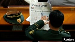 Một đại biểu quân đội đọc tờ China Daily trước phiên họp toàn thể lần thứ hai của Đại hội đại biểu Nhân dân toàn quốc (Trung Quốc) tại Bắc Kinh, ngày 9/3/2009. (REUTERS/David Gray)