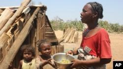 Toharano, une mère de 18 enfants se tient avec deux d'entre eux dans le village d'Ankilimarovahatsy, à Madagascar, le 9 novembre 2020.