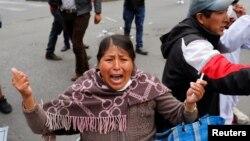 Reaksi seorang perempuan saat bentrok antara pendukung mantan presiden Bolivia Evo Morales dan anggota pasukan keamanan di La Paz, Bolivia, 13 November 2019.