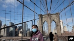 A woman wears a mask as she crosses the Brooklyn Bridge in New York, March 16, 2020. The bridge's pedestrian path is normally crowded on a sunny day.