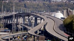 Several work vehicles are parked atop the West Seattle Bridge following an emergency closure several weeks earlier, April 15, 2020, in Seattle.