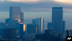 FILE - Pollution obscures the skyline of downtown as the sun rises over Denver, Feb. 28, 2019.
