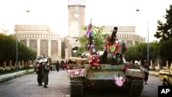 FILE - In this Sept. 28, 1996, photo, tanks manned by Taliban fighters and decorated with flowers are seen in front of the the presidential palace in Kabul, Afghanistan.
