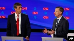 Former Texas Rep. Beto O'Rourke listens as former Colorado Gov. John Hickenlooper speaks during the first of two Democratic presidential primary debates hosted by CNN Tuesday, July 30, 2019, in the Fox Theatre in Detroit. (AP Photo/Paul Sancya)