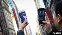 FILE - A company executive photographs a Luckin Coffee cup during the company's IPO at the Nasdaq Market site in New York, May 17, 2019.