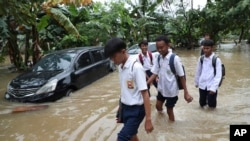 Students wade through a flood at a flooded neighborhood in Jakarta, Indonesia, Tuesday, Feb. 25, 2020. Overnight rains caused rivers to burst their banks in greater Jakarta sending muddy water into residential and commercial areas, inundating…
