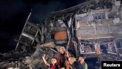 Grupo de personas gesticula cerca de los escombros de un edificio dañado mientras los palestinos celebran en las calles tras un alto el fuego, en la ciudad de Gaza el 21 de mayo de 2021.