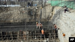 FILE - In this Feb. 10, 2020 photo, Afghan laborers work on a bridge project funded by the government, in Kabul, Afghanistan.