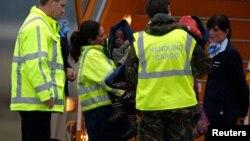 Ейндговен, 21 січня 2010 р. Стюарди та жінка, яка, як вважається, представляла голландську асоціацію усиновлювачів, супроводжують частину із 106 дітей з рейсту до Нідерландів з Порт-о-Пренса, Гаїіті