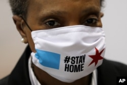 """FILE Chicago Mayor Lori Lightfoot wears a mask at a news conference in Hall A of the COVID-19 alternate site at McCormick Place in Chicago, April 10, 2020. The """"alternative care facility"""" is designed to relieve pressure on city hospitals."""