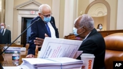Rep. Bill Pascrell, D-N.J., left, and Rep. Danny Davis, D-Ill., confer as the tax-writing House Ways and Means Committee continues working on a sweeping proposal for tax hikes on big corporations and the wealthy, at the Capitol, Sept. 14, 2021.