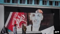 ພວກຜູ້ຊາຍຊາວອັຟການິສຖານຢືນຢູ່ໃກ້ຮູບຂອງປະທານາທິບໍດີ ອັຟການິສຖານ, ທ່ານ Ashraf Ghani ທີ່ຖືກສີກຂາດຢູ່ສະໜາມບິນສາກົນຂອງນະຄອນຫລວງກາບູລ, ວັນທີ 16 ສິງຫາ, 2021