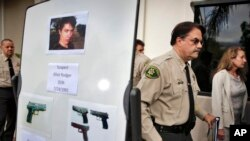 FILE - In this May 24, 2014 file photo, Santa Barbara County Sheriff Bill Brown, right, walks past a board displaying photos of gunman Elliot Rodger and the weapons he used in a mass shooting in Isla Vista, Calif.