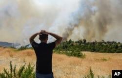 A man watches wildfires in Kacarlar village near the Mediterranean coastal town of Manavgat, Antalya, Turkey, July 31, 2021.
