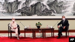 In this photo provided by the U.S. Department of State, U.S. Deputy Secretary of State Wendy Sherman, left, and Chinese Foreign Minister Wang Yi sit together in Tianjin, China, Monday, July 26, 2021. China came out swinging at high-level face-to…