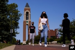 Masked students walk through the campus of Ball State University in Muncie, Ind., Thursday, Sept. 10, 2020. College towns across the U.S. have emerged as coronavirus hot spots in recent weeks as schools struggle to contain the virus. Out of nearly…