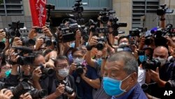 FILE - Hong Kong media tycoon Jimmy Lai, lower right, arrives at court for charges relating to unlawful protests from last year in Hong Kong, May 18, 2020.