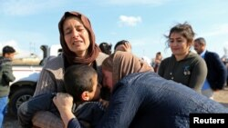 FILE - Relatives hug a Yazidi survivor following the boy's release from Islamic State militants in Syria, in Duhok, Iraq, March 2, 2019.